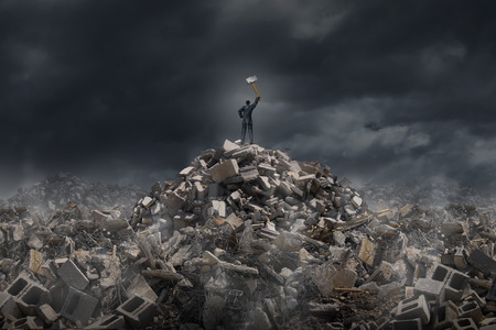 tearing down: Destroy and demolish concept as a businessman  standing on a mountain of  building ruins holding a sledge hammer as a business or life metaphor for tearing down old industry to make room for a modern infrastructure.