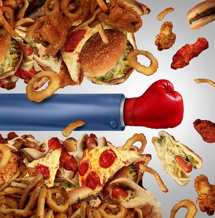 food fight: Fitness diet fight concept as a group of unhealthy junk food as hamburgers and fried fast foods being punched open by a person with a boxing glove as a symbol of fighting off cholesterol rich temptation. Stock Photo