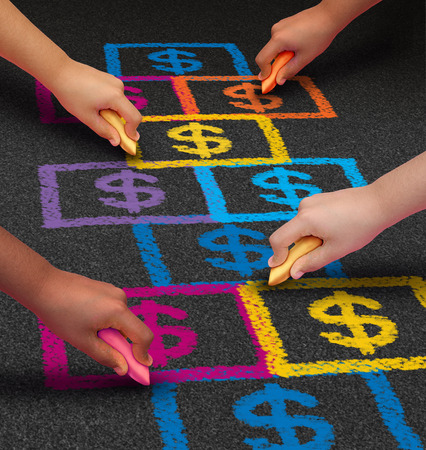 economy: School financing and education business concept as a group of children drawing a hopscotch game on a floor with dollar signs as a symbol of student loans and paying for schooling fees. Stock Photo
