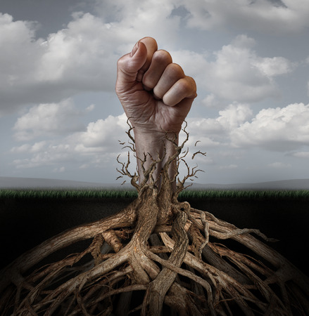 liberation: Addiction freedom and breaking out concept as a human hand in a fist escaping from tree roots that were holding it down as a symbol for human rights and fighting for individual independence and liberation. Stock Photo