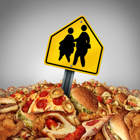 junk: Children diet problems and obesity crisis in the school concept as a heap of unhealthy fast food with two overweight fat kids on a a crossing traffic sign as a nutrition risk symbol for the youth.