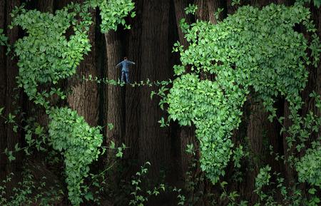Concepto de negocio de riesgo el crecimiento global como un hombre de negocios caminando sobre una cuerda floja hecha de vides de las plantas en un fondo de la hoja del árbol de los bosques en forma de vid como un mapa del mundo como una metáfora para el comercio internacional y la inversión de la incertidumbre o la conservación del medio ambiente es