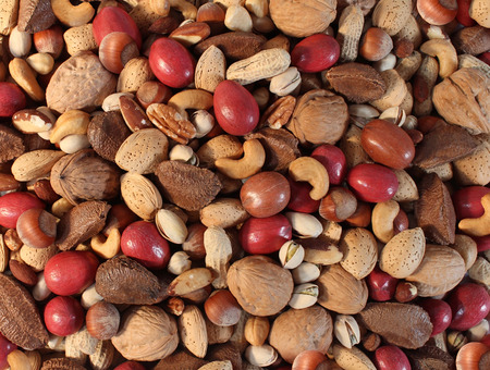 mixed nuts: Nuts background with a mixed assortment of seeds and pecan with walnut brazil nut peanut,hazelnut pistachio almond and cashew as a healthy food symbol and nutritious source of protien and lifestyle icon. Stock Photo