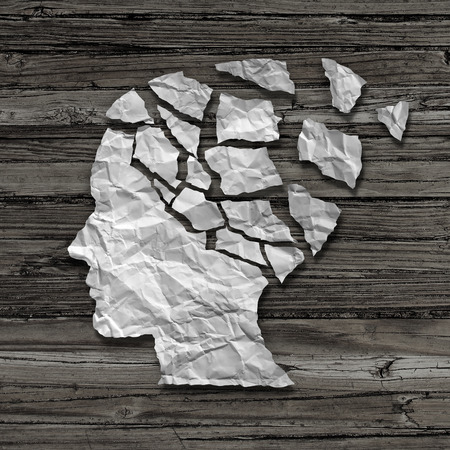 Alzheimer patient medical mental health care concept as a sheet of torn crumpled white paper shaped as a side profile of a human face on an old grungy wood background as a symbol for neurology and dementia issues or memory loss. Archivio Fotografico
