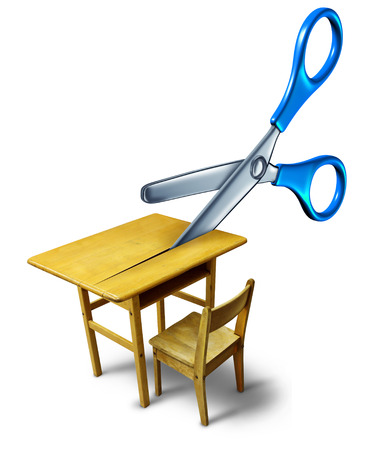 cut price: School budget cuts crisis concept and education cutbacks symbol as an old class desk being cut by scissors as a metaphor for belt tightening challenges with finances after a reduction in funding.