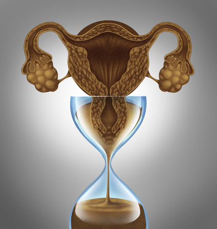menopause: Female biological clock concept as a uterus and ovaries from the anatomy of a woman  as falling sand in an hourglass as a metaphor for the anxiety stress and pressure to get pregnant before the aging process of  human menopause.