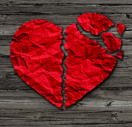 Broken heart breakup concept  as a separation and divorce icon as red crumpled paper shaped as a torn love on rustic old wood also a symbol of medical cardiovascular health care problems due to illness.