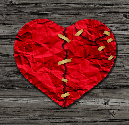 breakup: Heart therapy as a red crumpled paper shaped as a torn love icon that has been taped together as a metaphor for therapy and reconciliation on rustic old wood also a symbol of medical cardiovascular health care surgery due to illness.