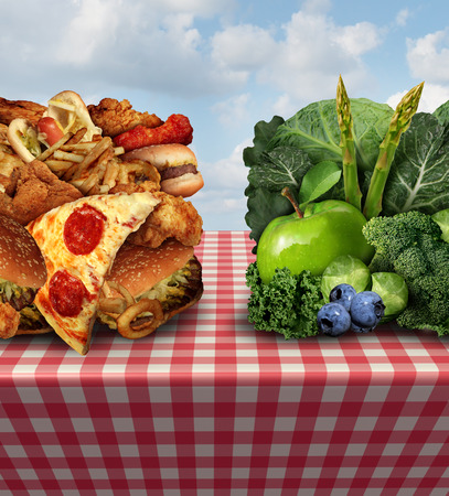 greasy: Healthy living concept and diet decision symbol or nutrition choices dilemma between healthy good fresh fruit and vegetables or greasy cholesterol rich fast food on a picnic table with a cloth trying to decide what to eat. Stock Photo