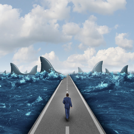 Headed for danger business concept as a man walking on a straight road towards a group of dangerous sharks as a metaphor and symbol of risk and courage from a person on a career path or life journey. Archivio Fotografico