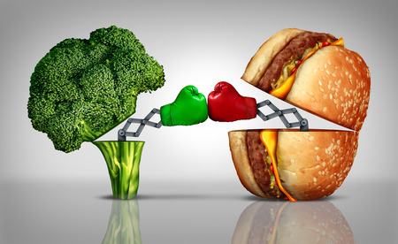 food fight: Food fight nutrition concept as a fresh healthy broccoli fighting an unhealthy cheese burger with boxing gloves emerging out of the meal options punching each other.