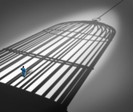 Feeling trapped in a prison concept as a person standing inside the cast shadow of a giant bird cage as a metaphor for business career frustration or human repression metaphor.