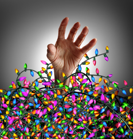 lights on: Holiday season stress concept as a human hand escaping from a chaotic tangled mess of decoration lights as a symbol of seasonal distress and social planning anxiety. Stock Photo