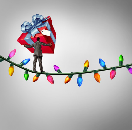 christmas debt: Holiday risk concept as a person holding a giant gift on a high wire tightrope made from christmas lights as a debt and credit metaphor and symbol of the challenges of giving. Stock Photo