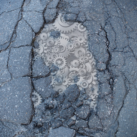 Public works and transportation concept as a broken asphalt road with gears and machine cog wheels as a metaphor and symbol for city and government administration of taxpayer services.