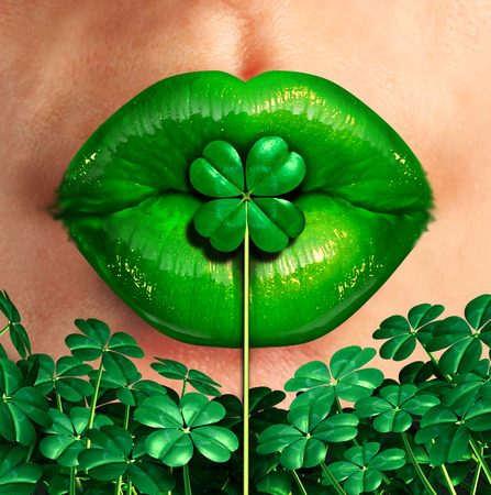 Spring kiss as emerald green lips kissing a four leaf shamrock clover as a st.patrick