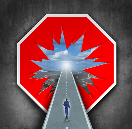 to break through: Business breakthrough and overcoming road blocks as a red and white stop sign with a hole revealing a path for a person to walk towards career or life success. Stock Photo