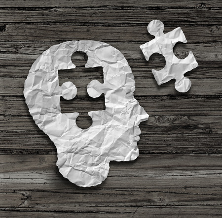 Puzzle head brain concept as a human face profile made from crumpled white paper with a jigsaw piece cut out on a rustic old wood background as a mental health symbol. Stockfoto