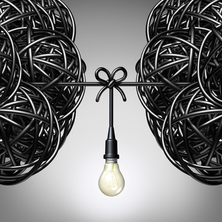 Team ideas and collaboration concept as two groups of tangled electric cord or wire with a light bulb connection tied together between the partners as a teamwork metaphor for success. Stock Photo