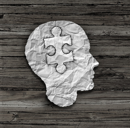 Puzzle head solution concept as a human face profile made from crumpled white paper with a jigsaw piece cut out inside the brain area on an old wood background as a mental health symbol. photo