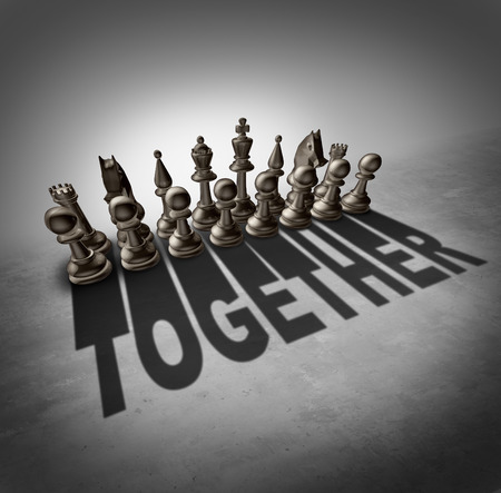 team effort: Together concept and team effort symbol as a group of chess pieces in a set casting a shadow with the word representing partnership solidarity in a company or union of workers.