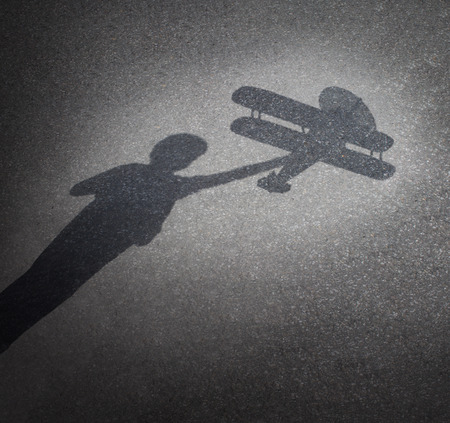 trave: Childhood aspirations concept as a cast shadow on pavement of a child playing with a toy plane as a symbol for dreaming and imagination through fun and learning as a happy kid.