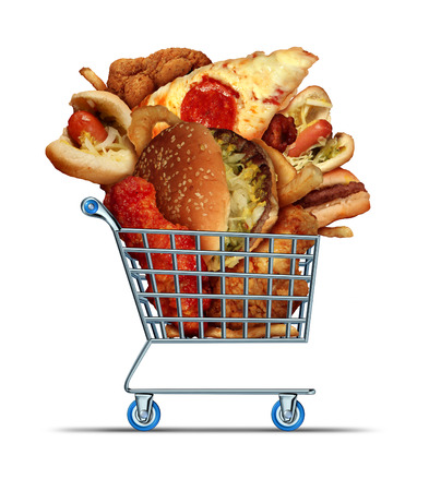 Unhealthy food shopping as a diet concept with greasy fried take out as onion rings burger and hot dogs with fried chicken french fries and pizza in a store shop cart as a symbol of consumer eating habits. Banco de Imagens