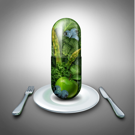 Food supplement concept as a giant pill or medicine capsule with fresh fruit and vegetables inside on a table place setting
