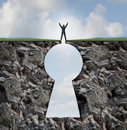 Businessman standing on keyhole mountain cliff as a person with arms up in victory on top of a rock mountain shaped as a key hole business and finance symbol for financial and life success. photo