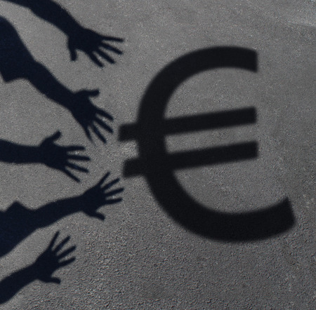 economic issues: Euro demand as the cast shadow of a group of hands reaching out to grab the European currency symbol as a financial and business concept or money financing issues and economic symbol. Stock Photo