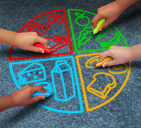 Food groups nutrition and healthy lifestyle concept as a group of diverse children holding chalk drawing a pie chart diagram on asphalt with protein dairy fruits and vegetables and starch symbols. Stockfoto
