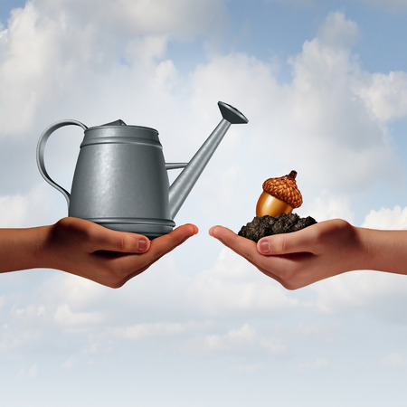 acorn seed: Watering can investing business concept as a two diverse human hands holding a water pot and an acorn seed in fertile soil as a financial metaphor for economic development or environmental collaboration and hope for the future.