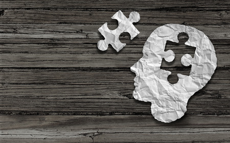 Mental health symbol Puzzle and head brain concept as a human face profile made from crumpled white paper with a jigsaw piece cut out on a rustic old double page spread horizontal wood background. Stock Photo