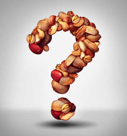allergy questions: Nut question mark with a mixed assortment of seeds and pecan with walnut brazil nut peanut,hazelnut pistachio almond and cashew as a symbol of confusion and allergy to nuts information or food facts icon. Stock Photo