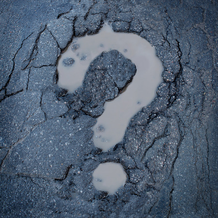 Road construction concept and city maintenance of infrastructure symbol as broken pavement or asphalt shaped as a question mark pot hole or damaged street as an icon for highway safety questions. Stockfoto