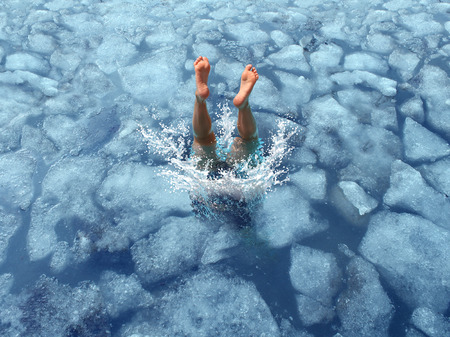 in action: Cool down and Cooling off concept as a diver diving into frozen ice water as a symbol for managing hot weather summer heat and refreshing break from a heatwave.