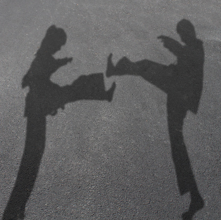 karateka: Karate children in a competitive combat as the cast shadow of a girl and boy fighting with leg kicks as martial arts for kid fitness and healthy activities symbol.