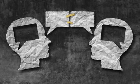 Speaking together social media concept as two crumpled pieces of paper shaped as a human head with talk bubbles or speech bubble icons taped as a communication symbol for business understanding and compromise agreement. photo