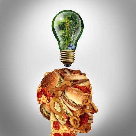 Diet Motivation and dieting inspiration concept as a human head made of greasy junk food with a lightbulb idea icon made of green fruits and vegetables as a nutrition and health care metaphor. 写真素材