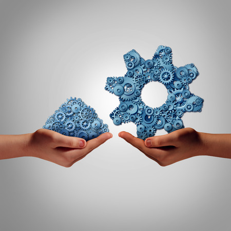 Technology management concept as a hand holding a group of mixed disorganized gears and cogs with another person presenting the machine parts put together as a symbol for a business manager connecting the ingredients for success.