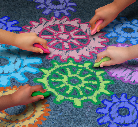 society: Education concept as a diverse community of children working together in friendship drawing connected gears and cog wheels with chalk as a symbol for the success of learning with a school program.