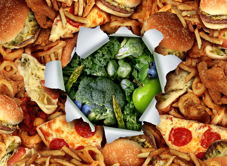 junk: Diet lifestyle change concept and breaking out and escape from unhealthy habits of eating fatty junk food towards green vegetables and fruit as a ripped and burst hole in the paper revealing healthy nutritious garden fresh produce.