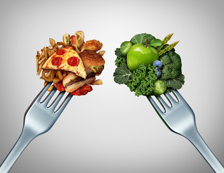 junk: Diet struggle and decision concept and nutrition choices dilemma between healthy good fresh fruit and vegetables or greasy cholesterol rich fast food with two dinner forks competing to decide what to eat.