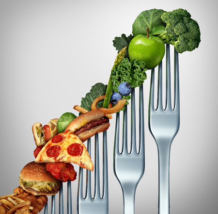 unhealthy diet: Diet progress change as a healthy lifestyle improvement concept and evolving to accept the challenge of eating raw food and losing weight as a group of rising forks with meal items on them from fatty food towards vegetables and fruit. Stock Photo