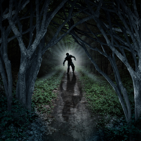 woods: Horror monster walking in a dark forest as a scary fantasy concept with a creepy thing coming out of a remote wilderness background with a moon glow behind it as a halloween fear symbol of haunted woods and panic anxiety. Stock Photo