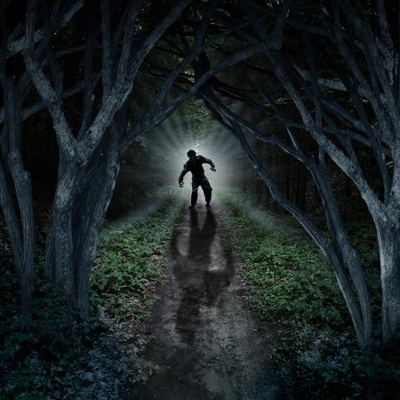 demonio: Horror monstruo caminando en un bosque oscuro como un concepto de la fantasía de miedo con una cosa espeluznante que sale de un fondo remoto y salvaje con un resplandor de la luna detrás de ella como un miedo de halloween símbolo del bosque encantado y pánico ansiedad.
