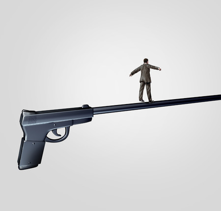 Gun risk concept and firearm social issue symbol as a person walking on the long barrel of a pistol as a highwire tightrope walker metaphor representing the danger and uncertainty of weapon management.