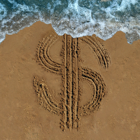 Financial loss business concept as a drawing of a money symbol drawn on a beach being washed out by an ocean wave as an economic icon for currency change or fading budget and laundering of finances.