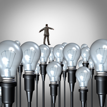 is creative: Creativity management concept and business idea challenge symbol as a businessman walking carefully on a group of lightbulbs as a success metaphor to manage and guide creative thinking. Stock Photo