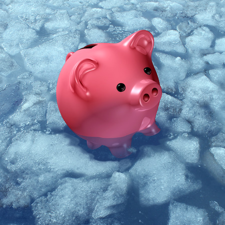 liquidity: Frozen asset and budget freeze business concept or freezing wages financial symbol as a piggybank or piggy bank in ice and sinking in cold arctic water as a finance icon for not being able to sell an investent or redeem a fund.